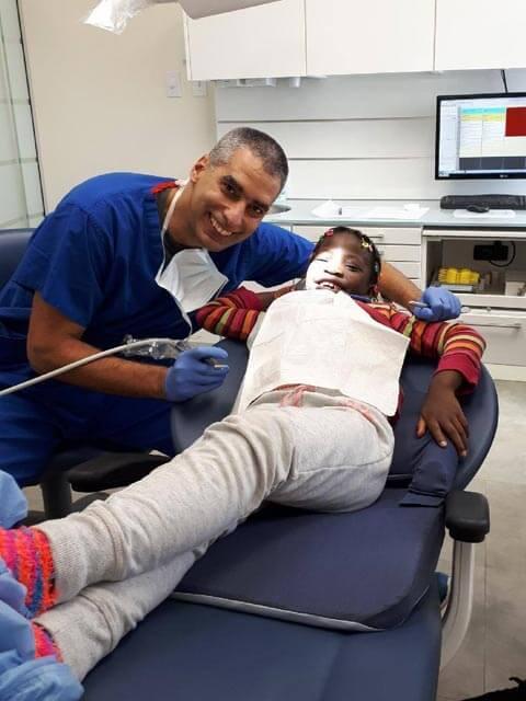 Dr Éric Lacoste offrant des soins dentaires à un enfant dans le cadre du Mouvement Grandir Ensemble